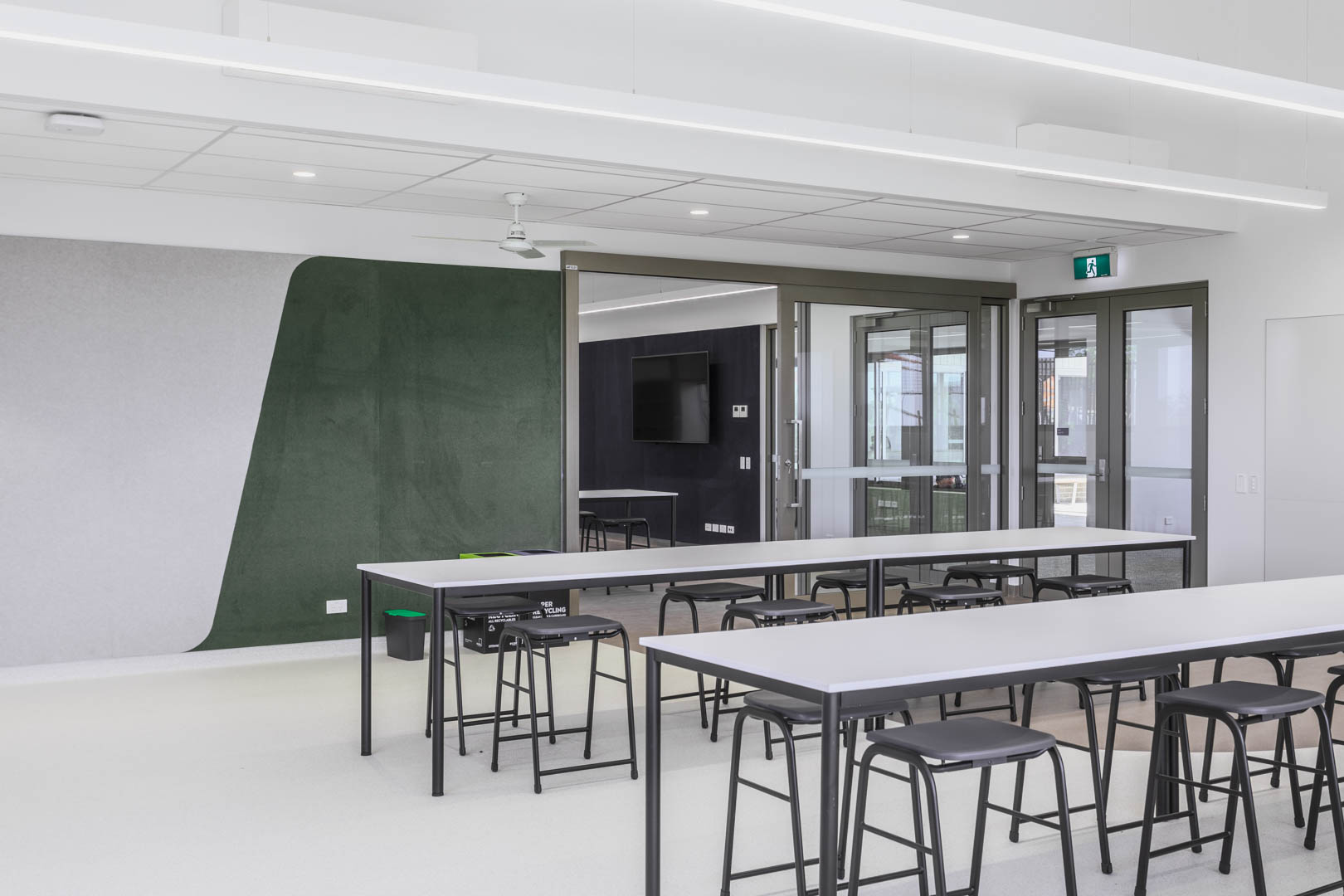 an open acoustic glazed sliding door inside a school